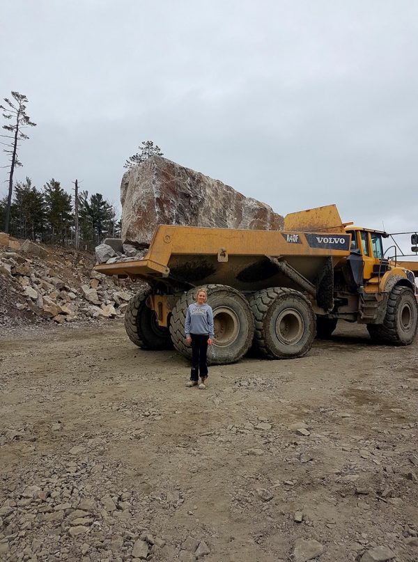 rental dump truck with large boulder loaded