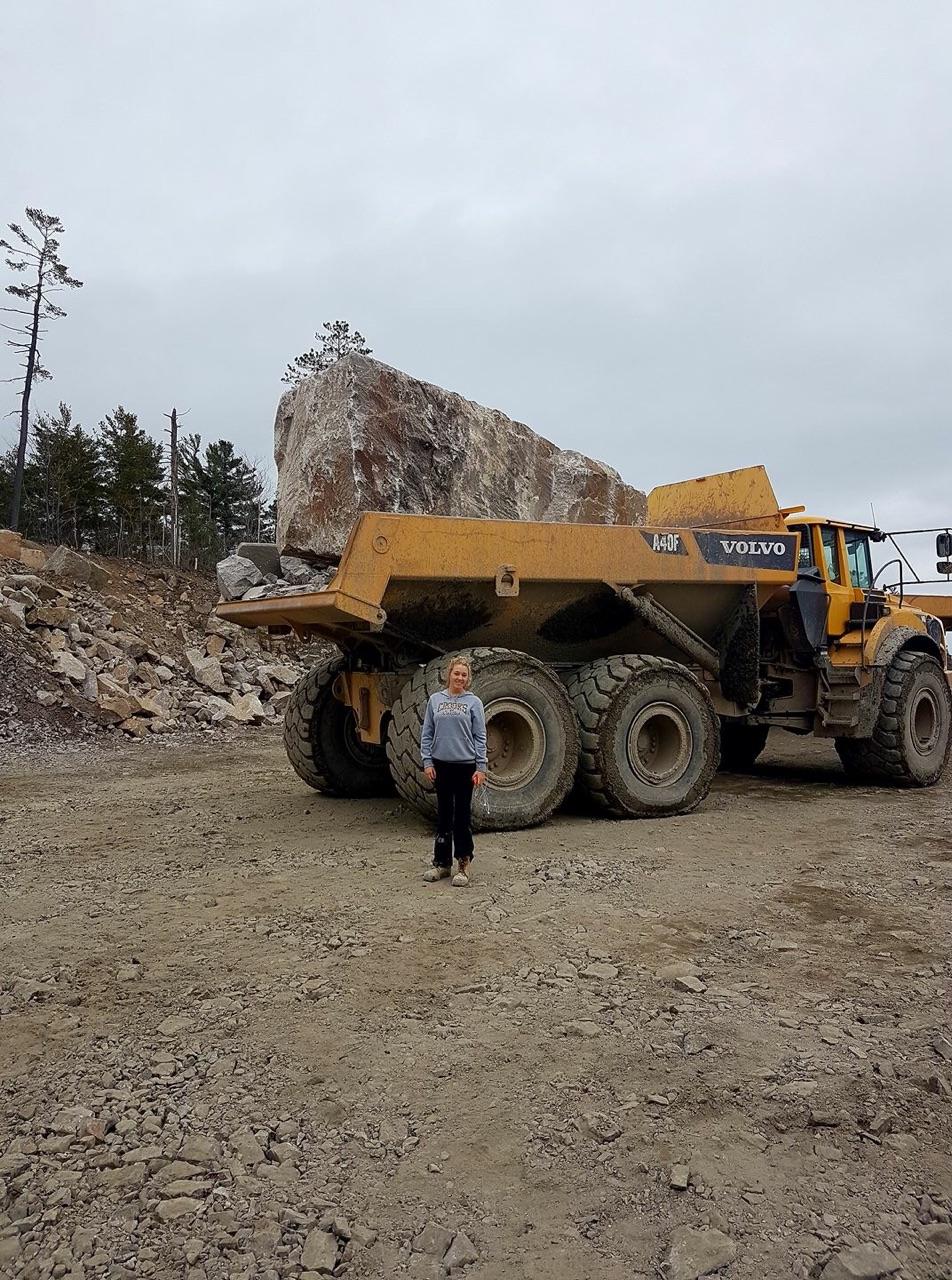 rental dump truck with large boulder loaded
