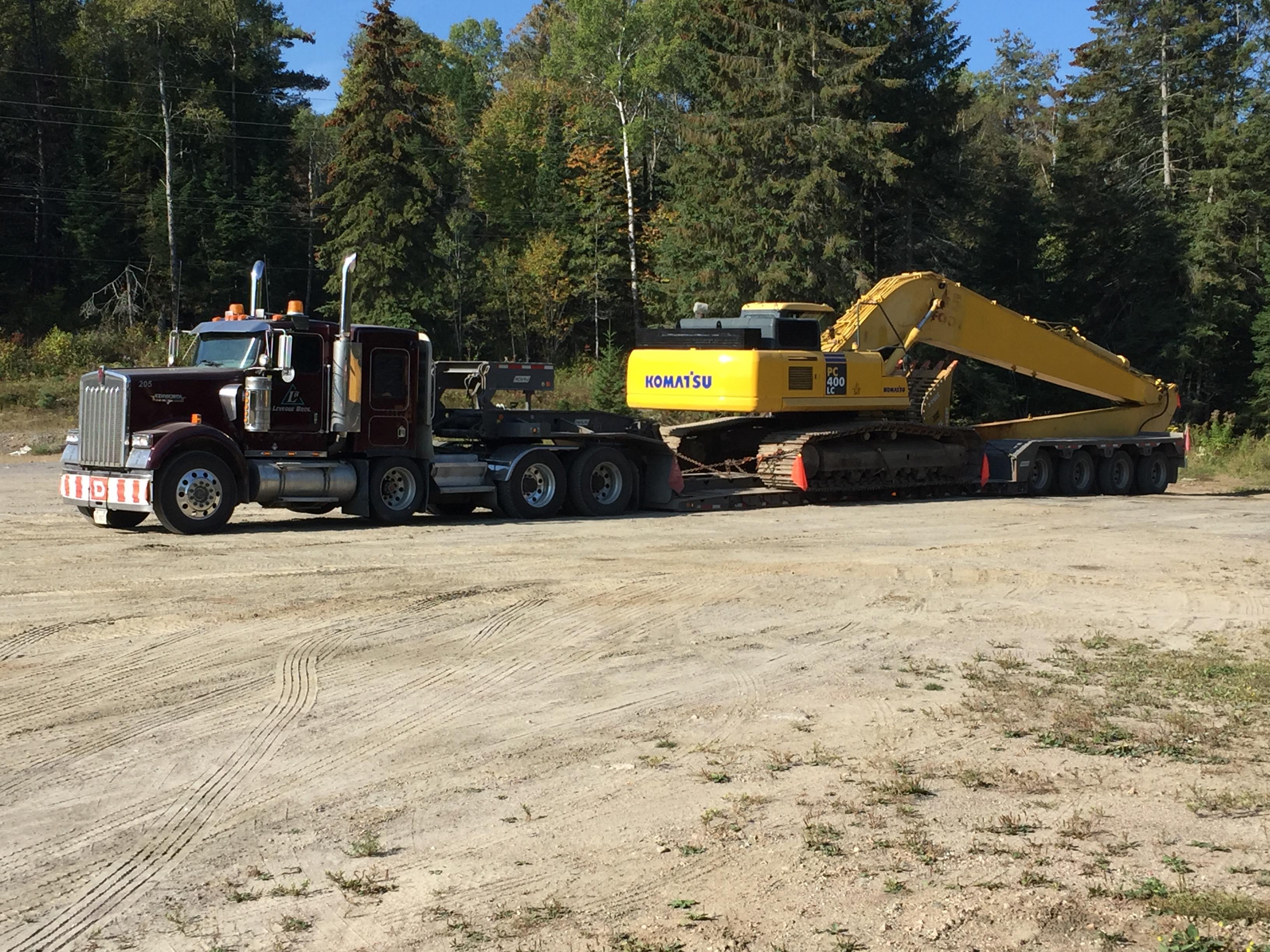 excavator rental delivered on semi truck flatbed